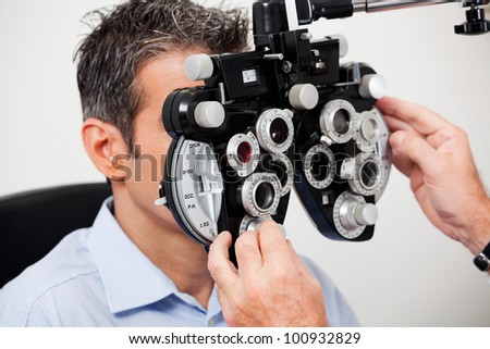 Optometrist adjusting panels of phoropter while examining his patient - stock photo