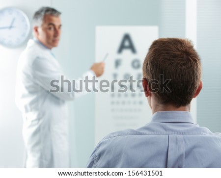 Optometrist and patient, doctor pointing at eye chart  - stock photo
