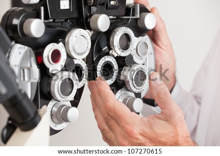Optometrist changing settings in phoropter before an eye test - stock photo
