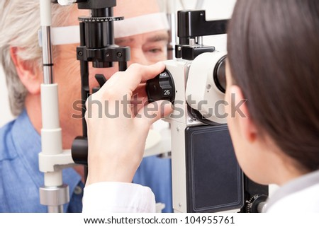 Optometrist doing sight testing for pateient. - stock photo