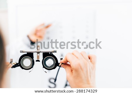 Optometrist doing sight testing for patient - stock photo