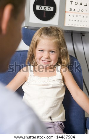 Optometrist in exam room with young girl in chair smiling - stock photo