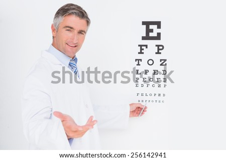 Optometrist looking at camera in medical office - stock photo