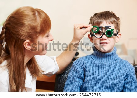 Optometry concept. female doctor ophthalmologist or optometrist helps young boy with phoropter during sight testing or eye examinations in clinic - stock photo