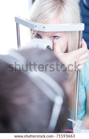 optometry concept - pretty young female patient having her eyes examined by an eye doctor (color toned image; shallow DOF) - stock photo