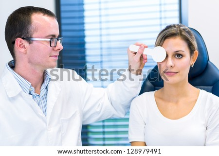 Optometry concept - pretty young woman having her eyes examined by an eye doctor - stock photo