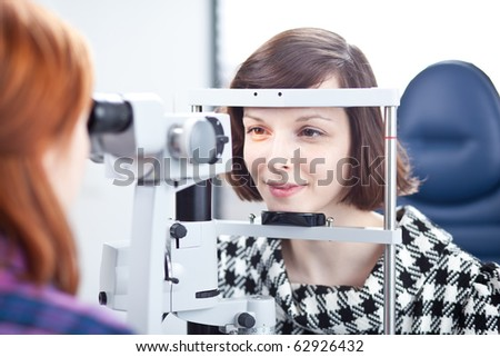 optometry concept - pretty young woman having her eyes examined by an eye doctor (color toned image) - stock photo