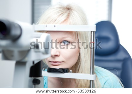optometry concept - pretty young woman having her eyes examined by an eye doctor on a slit lamp - stock photo