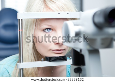 optometry concept - pretty young woman having her eyes examined by an eye doctor on a slit lamp