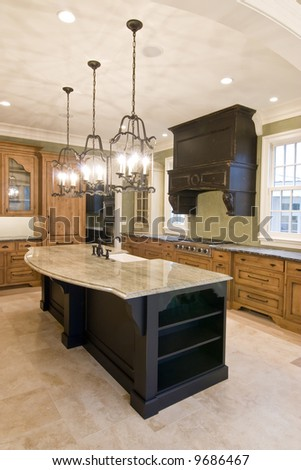 opulent kitchen with complimentary colored cabinets and granite island - stock photo