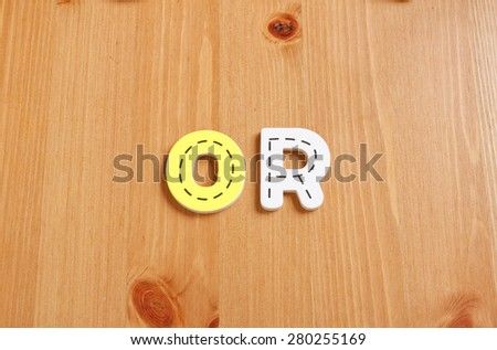 OR, spell by woody puzzle letters with woody background - stock photo