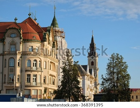 ORADEA, ROMANIA - JULY 31, 2015: elegant buildings and bell tower of St. Ladislaus Roman-Catholic Church in Union Square of Oradea.   - stock photo