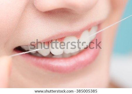 Oral hygiene and health care. Smiling women use dental floss white healthy teeth. - stock photo