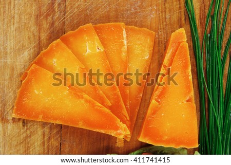 orange aged delicious cheddar cheese chop with slice on wooden plate with tomatoes , chives and salad . isolated over white background - stock photo