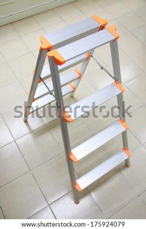 orange aluminum folding ladder, stepladder on tile floor for general repair - stock photo