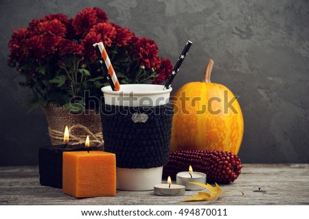 Orange and black lit candles, mug, pumpkin and autumn home decor with rustic wood background