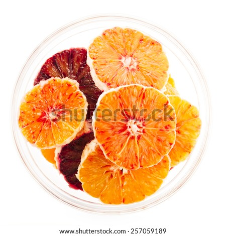 Orange and blood orange slices in glass bowl isolated on white - stock photo