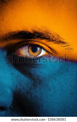 Orange and blue flag painted on face of a sport team supporter, close up of a male eye. - stock photo