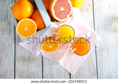 Orange and carrot juice in glasses on napkin and fresh fruits in wooden box on wooden background - stock photo