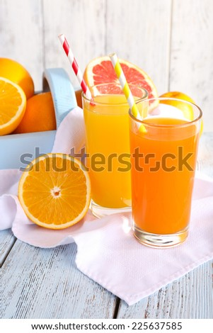 Orange and carrot juice in glasses on napkin and fresh fruits in wooden box on wooden table on wooden wall background - stock photo