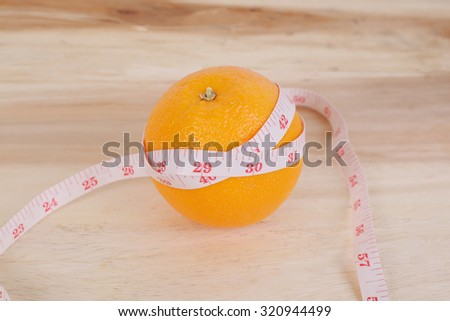 orange and centimeter on wood back ground for lose weight concept - stock photo