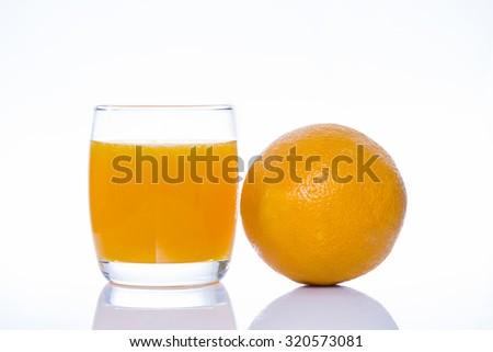 Orange and glass of orange juice on white background - stock photo