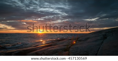 Orange and gray evening seascape. Lake Onega Waves beat against the stone shore which reflects the rays of the setting sun on the background of a dramatic stormy sky. - stock photo