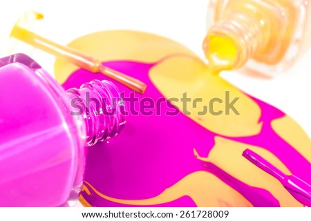 Orange and pink nail polish bottles with nail polish pouring from them on the white background - stock photo