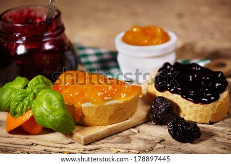 orange and plum jam with slices of bread on wooden table  - stock photo