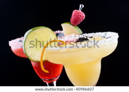 Orange and Raspberry margaritas in chilled glass over black background on reflection surface, garnished slice of fresh lime, orange, and raspberries. Most popular cocktails series. - stock photo
