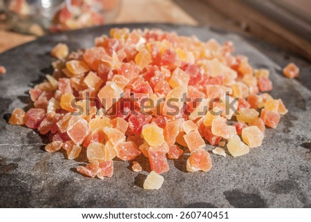 Orange and red dried papayas on a stone plate - stock photo