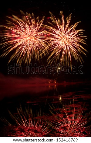 Orange and Red Fireworks reflected in a murky lake - stock photo
