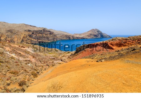 Orange and red lava soil hills and rocks with ocean bay view from trekking trail on Punta de Sao Lourenco peninsula, Madeira island, Portugal - stock photo