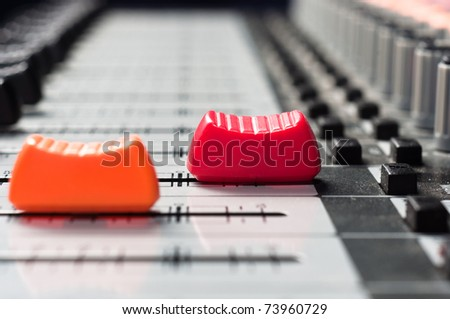 Orange and  red slider on a sound mixer with blurry background - stock photo