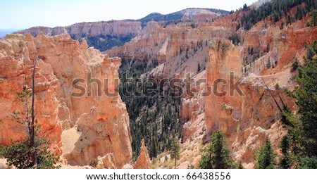 Orange and red spires of eroded sandstone rock formations decorate the canyon landscape with vibrant colorful shapes at Bryce National Park