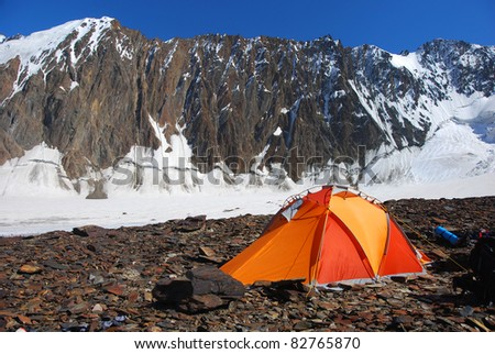 Orange and red tent on the glacier in high mountains - stock photo