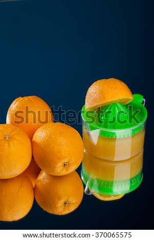Orange and squeezer on blue background - stock photo