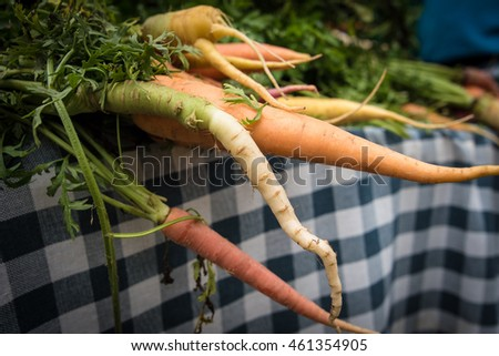 Orange and white carrots for sale at a farmers' market.