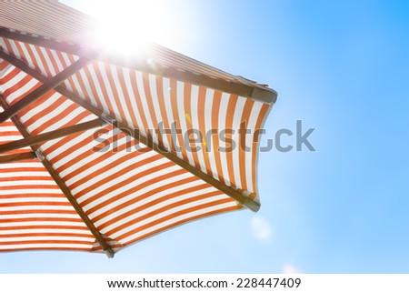 Orange and white striped beach umbrella with natural sun flare - stock photo