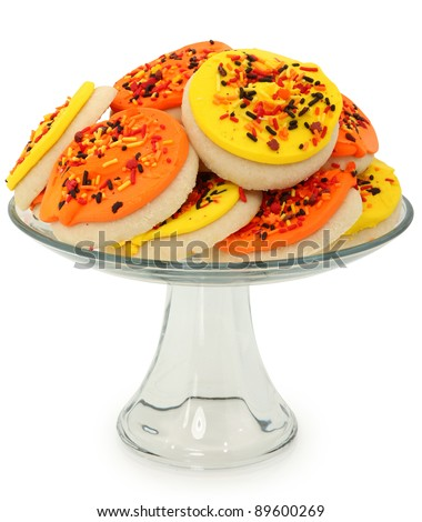 Orange and yellow autumn decorated sugar cookies on glass platter over white.