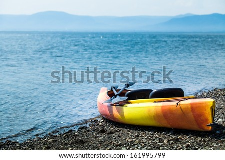 Orange and Yellow Kayak With Oars on the Sea Shore During a beautiful Day of Summer - stock photo