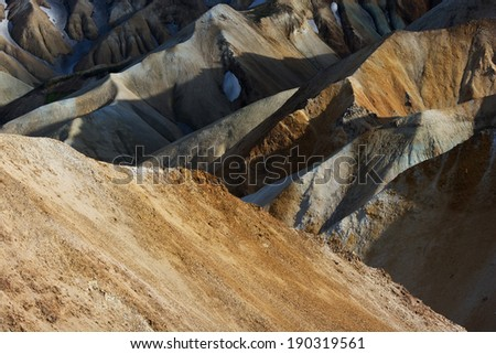 Orange and yellow mountain peaks captured from above in Landmannalaugar on a sunny summer day, Iceland