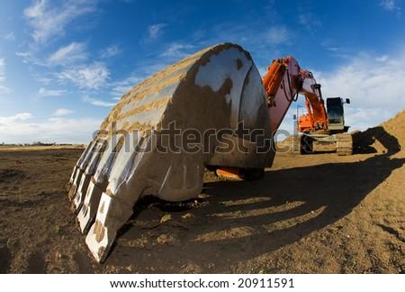 Orange backhoe parked at a construction site - stock photo