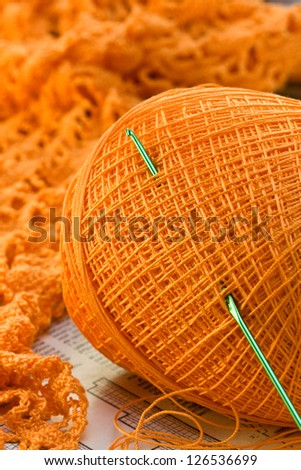 orange ball of yarn, a hook, a knitted fabric