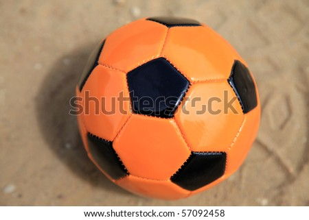 orange ball with black pentagon sign on the sand playing field - stock photo