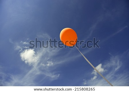 orange balloon flying in the blue sky - stock photo