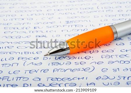 Orange ballpen on a letters background - stock photo
