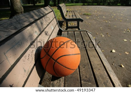 orange basket-ball ball on bench in a parka - stock photo