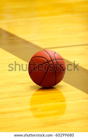 orange basket ball on yellow court at break time - stock photo