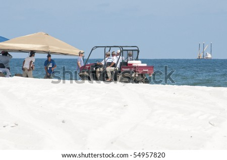 ORANGE BEACH, AL - JUNE 10:  Oil spill workers attempt to clean up oil along the beach in a tourist resort on June 10, 2010 in Orange Beach, AL. The beach is empty except for the workers in the height of the tourism season. - stock photo